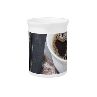View close-up on white cup of coffee and gloves drink pitcher