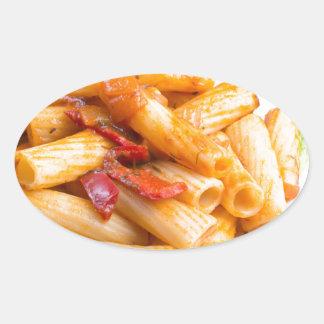 View closeup on a dish of rigatoni pasta oval sticker