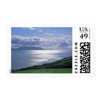 view of a grassy slope by the sea postage