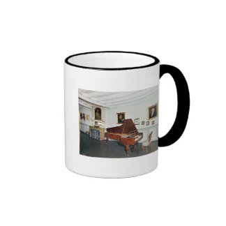 View of a room with a grand piano coffee mugs