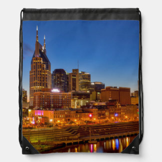 View of the city skyline at dusk drawstring backpack
