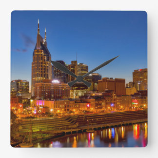 View of the city skyline at dusk square wall clock