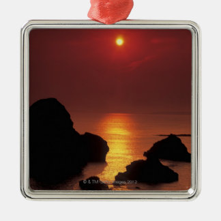 view of the sun setting over the sea metal ornament