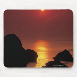 view of the sun setting over the sea mouse pad