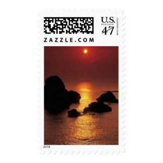 view of the sun setting over the sea postage