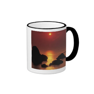 view of the sun setting over the sea ringer coffee mug
