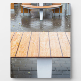 View tables wet after the rain in a cafe plaque
