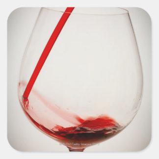 Vino rojo que vierte en el vidrio, primer pegatina cuadrada