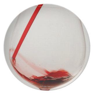 Vino rojo que vierte en el vidrio, primer platos