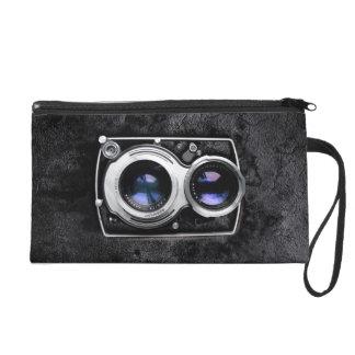 Vintage camera on black leather grunge wall