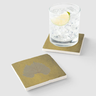 Vintage dusty grey dry leaf on yellowish brown stone coaster