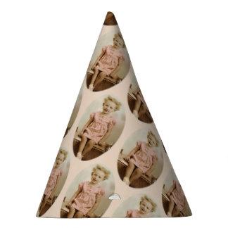 Vintage little blonde girl in pink dress party hat