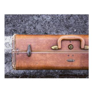 Vintage, maleta llevada en el lado del camino postales