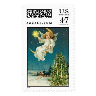 Vintage old fashioned angel sitting on moon postage