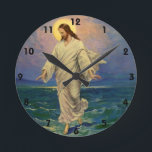 "Vintage Religion, Jesus Christ is Walking on Water Round Clock<br><div class=""desc"">Vintage illustration religious Christianity design featuring one of the miracles of Jesus in the New Testament, Jesus Christ walking on water. The young man is wearing a long flowing robe and has a holy halo or aura surrounds his head while he is walking across a sea or ocean with gentle...</div>"