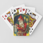"""Vintage Santa Claus Checking List Playing Cards<br><div class=""""desc"""">This vintage image is an old fashioned Santa Claus dressed in the traditional red cape outfit. He is checking his list holding some golden toys. He is surrounded by glowing candles, framed in ivy with a blue background with stars. See my store Art by MAR for matching products with this...</div>"""