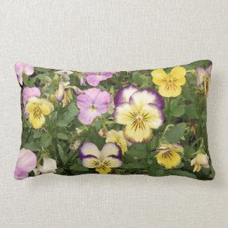 Violetas púrpuras y amarillas en verde almohada