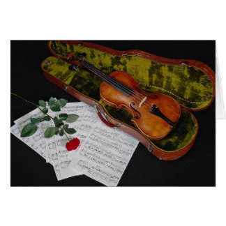 Violin and red rose on black background greeting card