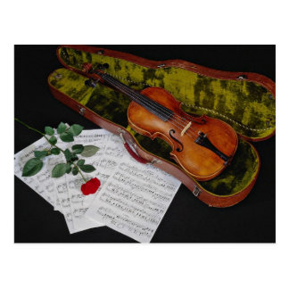 Violin and red rose on black background postcard