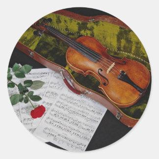 Violín y rosa rojo en fondo negro pegatina redonda