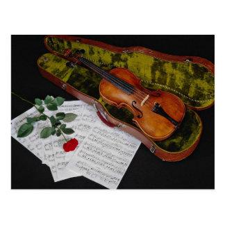 Violín y rosa rojo en fondo negro postales