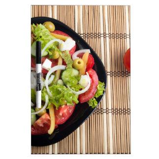 Vista aérea de una porción de ensalada vegetal pizarras blancas
