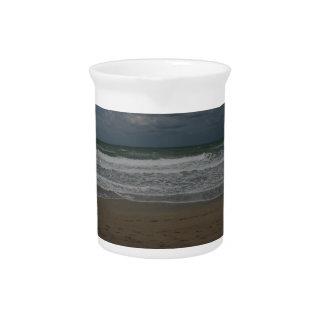 Vista al mar tempestuosa de la playa jarras de beber