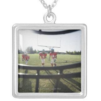 Vista de los futbolistas y del campo desde adentro collar plateado