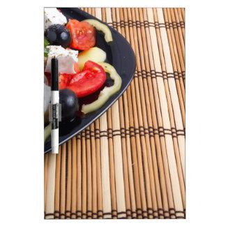 Vista lateral de la ensalada vegetariana griega pizarra blanca