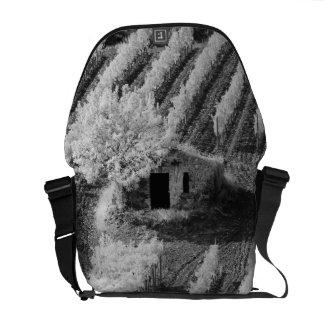 Vista negra y blanca del pequeño granero de piedra bolsas messenger