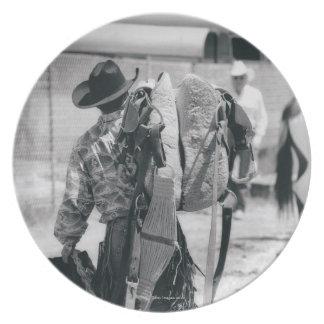 Vista posterior del vaquero que acarrea el engrana plato de comida