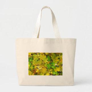 Vista superior de hojas amarillas y verdes bolsa tela grande