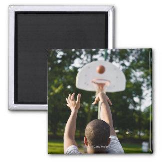 Vista trasera del baloncesto del tiroteo del hombr imán cuadrado