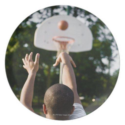Vista trasera del baloncesto del tiroteo del hombr plato para fiesta