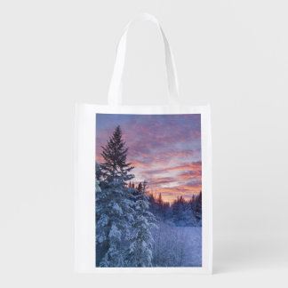 Vivid sunset paints the sky above wintery grocery bag