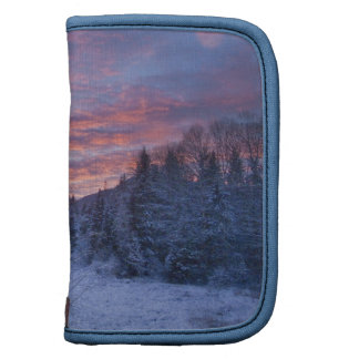 Vivid sunset paints the sky above wintery folio planners