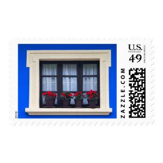 Vivienda residencial con las flores en ventanas estampilla