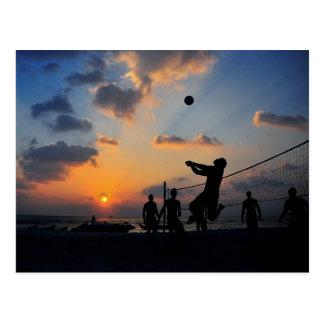Voleibol de playa en la puesta del sol postal
