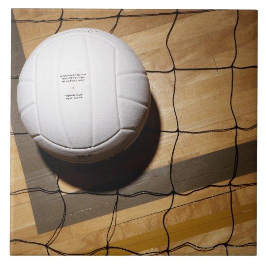 Voleibol y red en suelo de parqué de azulejo cuadrado grande