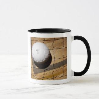 Volleyball and net on hardwood floor mug