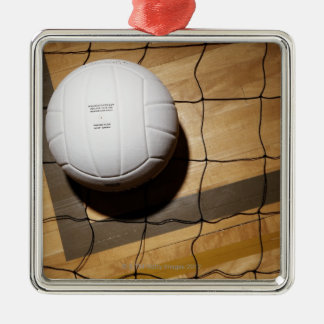 Volleyball and net on hardwood floor of square metal christmas ornament