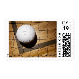 Volleyball and net on hardwood floor of postage