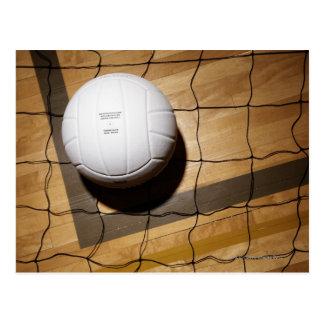 Volleyball and net on hardwood floor of postcard