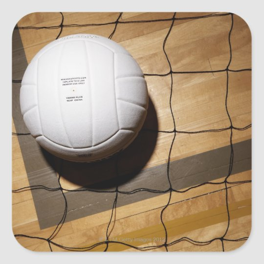 Volleyball and net on hardwood floor of square sticker