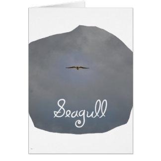Vuelo de la gaviota en un cielo gris con la tarjeta pequeña