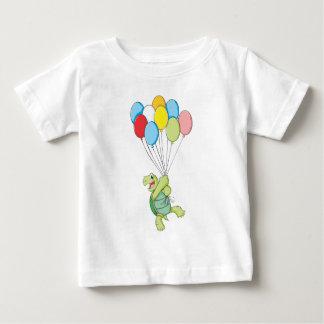 Vuelo feliz de la tortuga en los globos playera para bebé