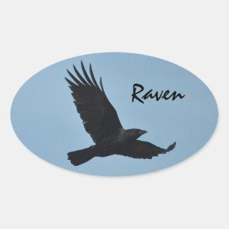 Vuelo negro del cuervo en foto del cielo azul pegatina ovalada