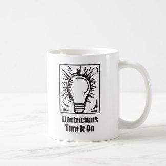 Vuelta de los electricistas él encendido taza de café