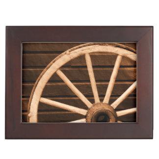 Wagon wheel leaning against old wooden wall keepsake box