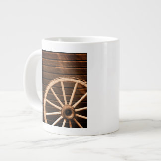 Wagon wheel leaning against old wooden wall large coffee mug